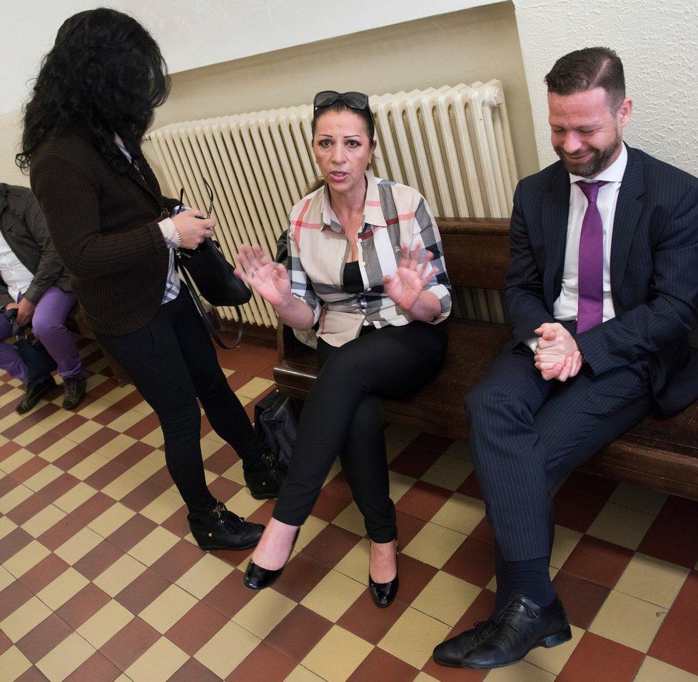 Nora Mojsejová u soudu se svým právníkem a mužem s dlouhými vlasy.
