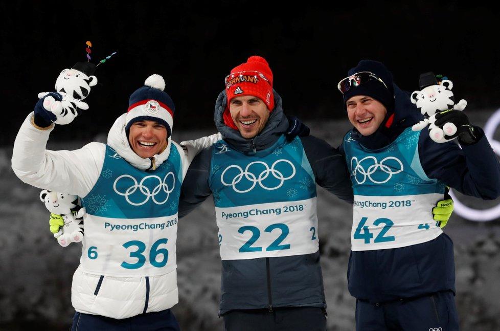 Stupně vítězů po sprintu biatlonistů na olympiádě v Pchjongčchangu. Vlevo se raduje stříbrný Michal Krčmář