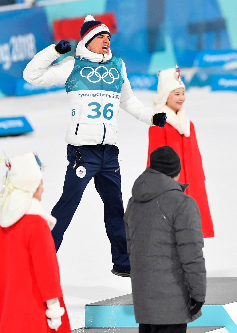 Michal Krčmář v euforii skáče na stupně vítězů při květinovém ceremoniálu