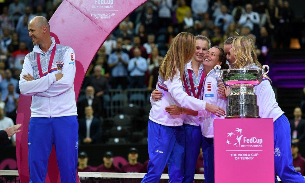 České tenistky se objímají u poháru pro vítězky Fed Cupu, zatímco kapitán Petr Pála si užívá triumf kousíček opodál...