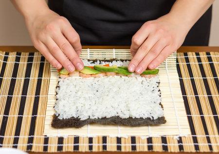 Na stůl rozložíme bambusovou podložku, na ni mírně navlhčenou řasu nori lesklou stranou dolů a rozprostřeme na ni v tenké vrstvě připravenou rýži.