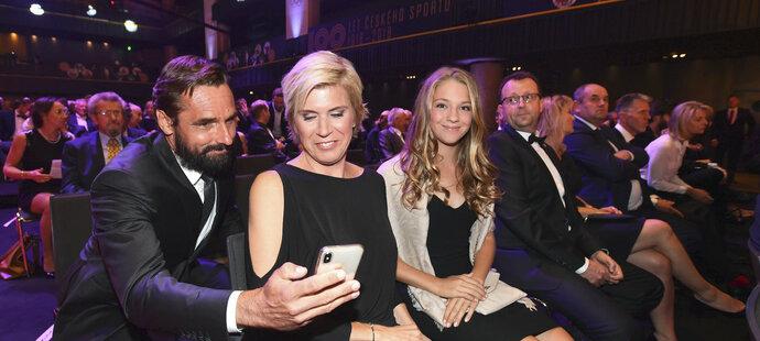 Roman Šebrle ukazuje něco na mobilním telefonu Kateřině Neumannové, se kterou společně ovládl sportovní moment desetiletí