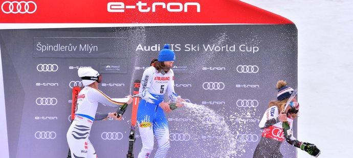 Mikaela Shiffrinová utíká před sprškou šampaňského od vítězné Petry Vlhové a druhé Němky Rebensburgové
