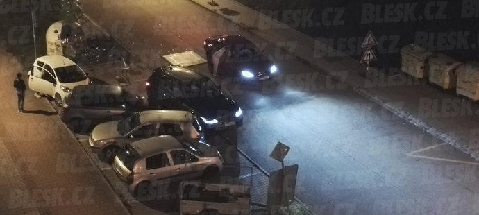Místo činu. Krmenčíkův černý land rover rozstřelil kontejner a vyřádil se na autech. Žena nahlížející do vozu, který přijel před policií, je podle svědka Michaelova manželka Denisa