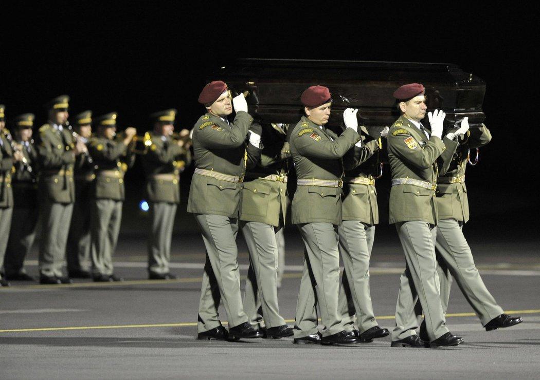 Šest členů čestné stráže nese rakev na letišti v Kbelích