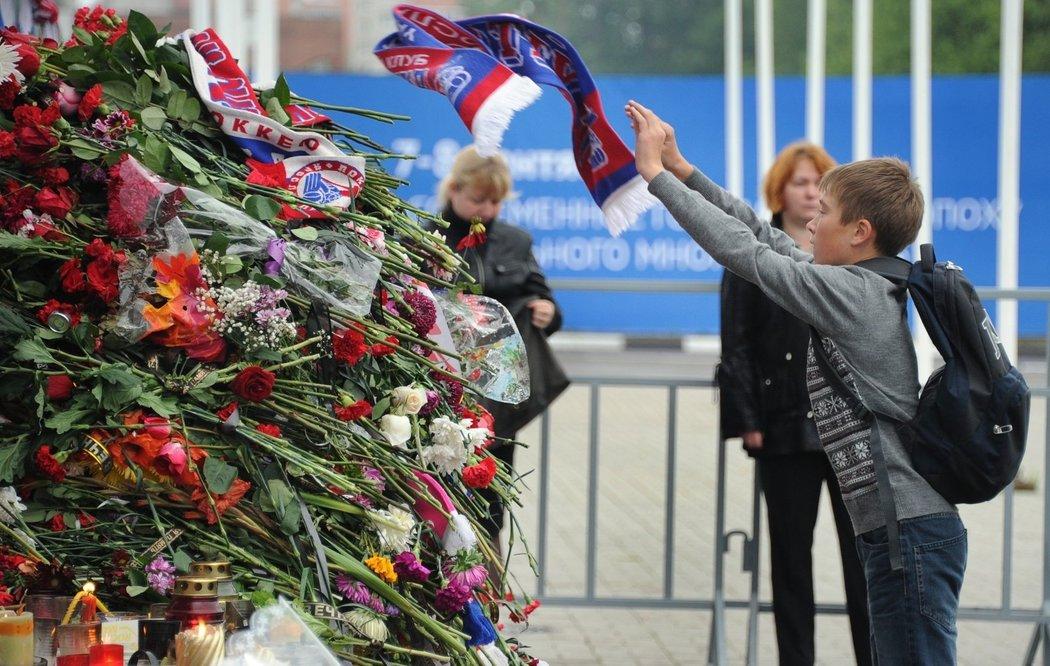 Jeden z malých fanoušků hází svou šálu Lokomotivu na hromadu květin a dalších vzpomínkových předmětů před hokejovou arénou v Jaroslavli
