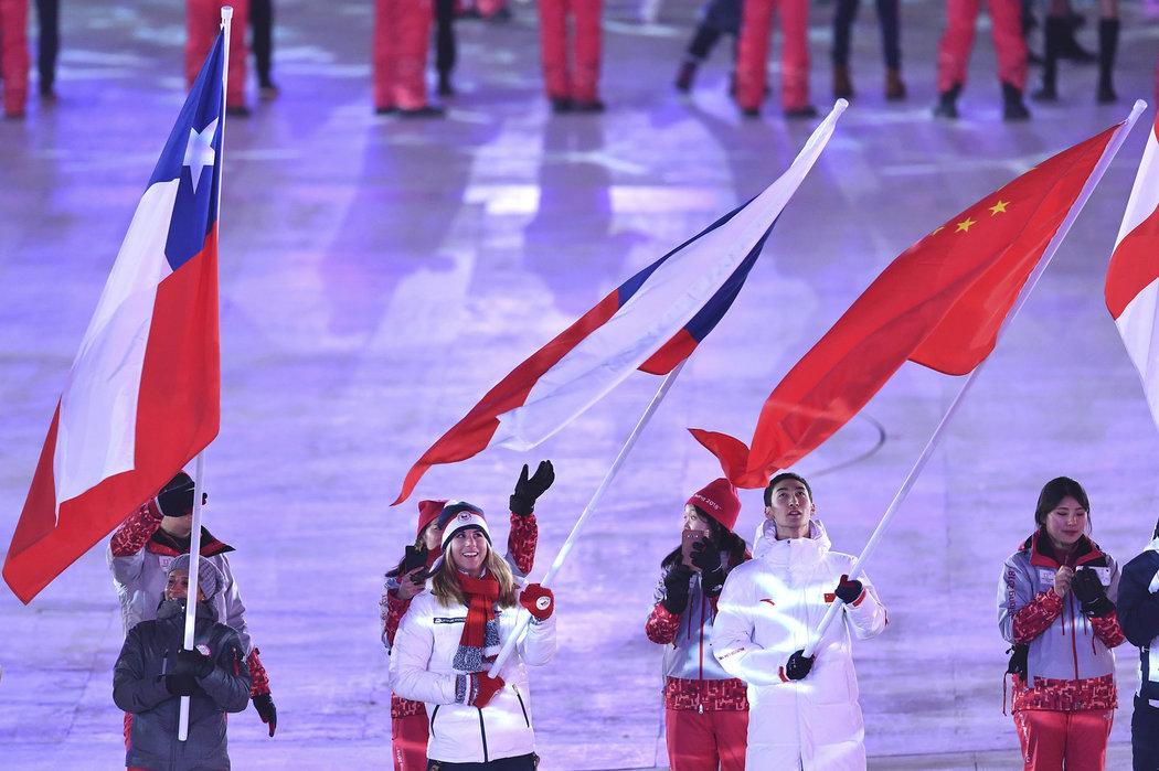 Ester Ledecká přichází s českou vlajkou na stadion při závěrečném ceremoniálu olympiády