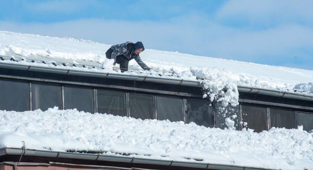 Horolezci se snaží odklidit přívaly sněhu ze střechy kladenského zimního stadionu