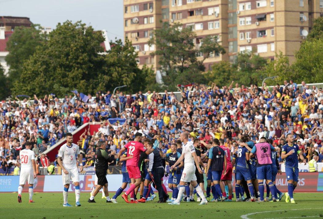 Zklamaní čeští fotbalisté po prohře v Kosovu, jehož hráči se v pozadí radují z výhry 2:1