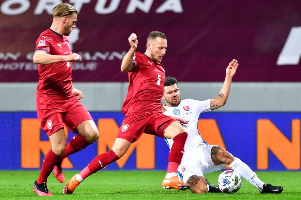 Český obránce Vladimír Coufal (uprostřed) v souboji o míč se Slovákem Michalem Ďurišem. Všemu přihlíží Tomáš Kalas